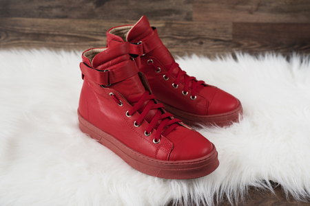 carpet and flooring: Red leather sneakers on a white carpet and wood flooring. Wooden background