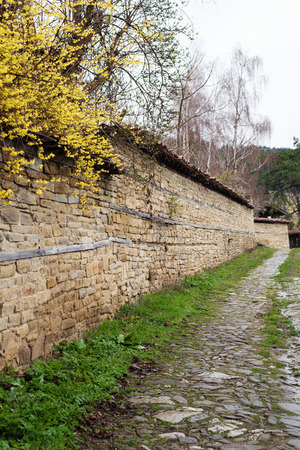 ethnographic: Stone Wall and yellow flowers. Street with cobble stones of folk museum Zheravna village in Bulgaria. Mountain village.