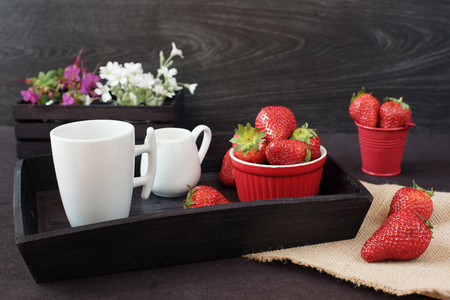 valentinas: Coffee and strawberries on wooden tray over black table. White and purple flowers in a decorative wooden crate. Black background