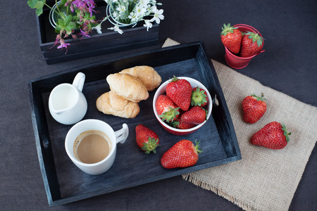 valentinas: Coffee, mini French pastries and strawberries on wooden tray over black table. White and purple flowers in a decorative wooden crate. Black background