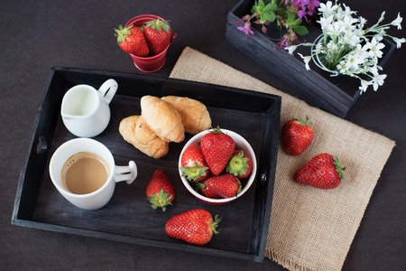 Coffee, mini French pastries and strawberries on wooden tray over black table. White and purple flowers in a decorative wooden crate. Black background
