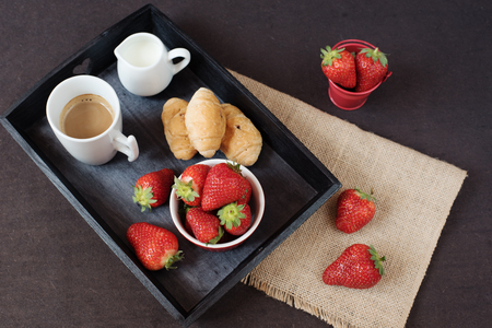 valentinas: Coffee, mini French pastries and strawberries on wooden tray over black table. Black background