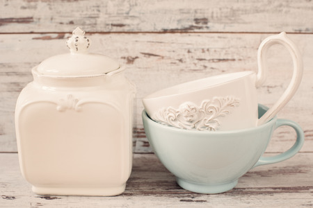 tinting: Simple rustic white and blue crockery, empty dishes. Two large bowls each other and porcelain jar with lid. Wooden background, shabby chic, vintage tinting Stock Photo