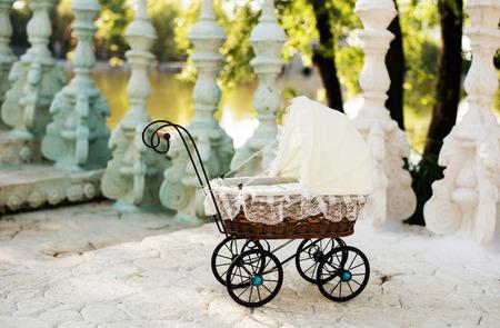 muneca vintage: cochecito de niño de la muñeca. cochecito de muñeca de la vendimia se coloca en las escaleras de un hermoso lago. muñecos carrito de retro de rattan y encaje blanco. Foto de archivo