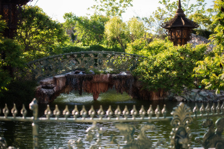footbridges: Beautiful bridge over the lake in green park. Beautiful pond and footbridges surrounded with trees and flowers. Stock Photo