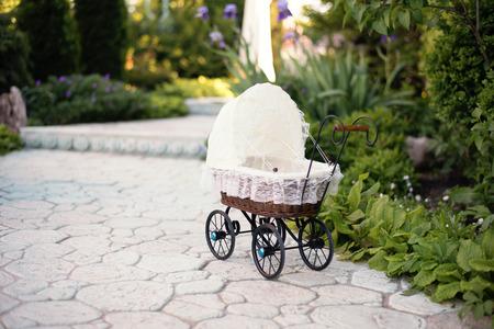 muneca vintage: cochecito de niño de la muñeca. cochecito de muñeca de la vendimia colocado en el camino de piedra, callejón en un hermoso jardín con flores y árboles alrededor. muñecos carrito de retro de rattan y encaje blanco