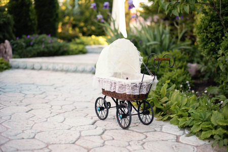 muneca vintage: Dolls pram. Vintage doll stroller placed on the stone walkway, alley in a beautiful garden with flowers and trees around. Retro cart dolls made of rattan and white lace