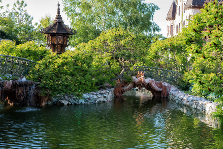 footbridges: Beautiful lake,  wrought iron fence and a green garden flowers and trees around. Outside, a park. Fairy lake and footbridges surrounded with trees.