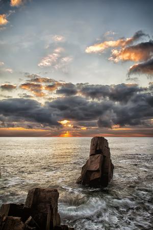 steep: Sunrise over a rocky beach. Colorful clouds reflecting in the sea. Dramatic sunrise over the Black Sea, Bulgaria
