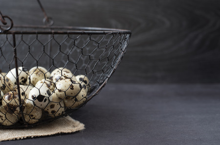 space for type: Wire mesh basket with quail eggs. Dark food photography. Rustic background, selective focus and diffused natural light. A different type of concept image for Easter. Copy space.
