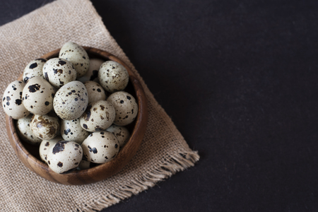 space for type: Wooden bowl with quail eggs. Dark food photography. Rustic background, selective focus and diffused natural light. A different type of concept image for Easter. Copy space.