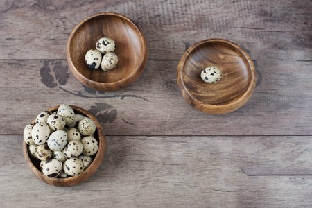 space for type: Three wooden bowls with quail eggs. Rustic wood background, diffused natural light. A different type of concept image for Easter. Copy space. Stock Photo