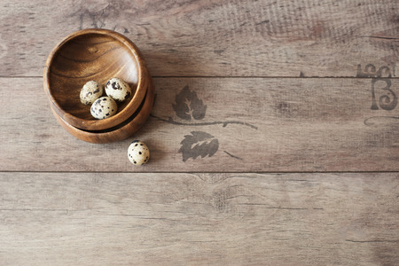 space for type: Wooden bowls with quail eggs. Rustic wood background, diffused natural light. A different type of concept image for Easter. Copy space. Stock Photo