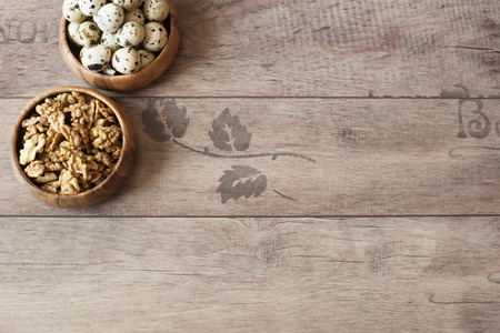 space for type: Walnuts and quail eggs in wooden bowls. Rustic wooden background, diffused natural light. Protein nutrients. A different type of concept image for Easter. Copy space.