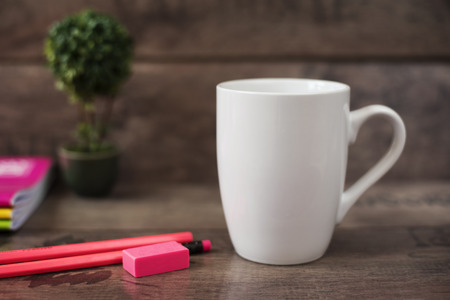 White mug mockup. Blank mug. Coffee mug mockup with bright neon colors pencils and notebooks. Potted plant bonsai behind. Rustic wooden background. Imagens