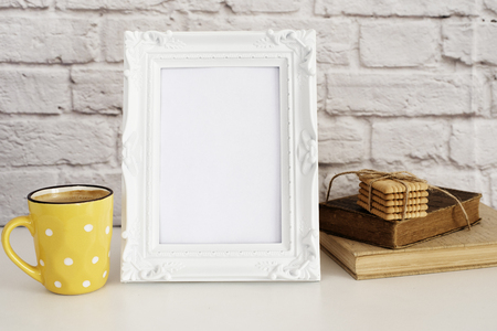 stock photography: Frame Mockup. White Frame Mock Up. Yellow Cup Of Coffee With White Dots, Cappuccino, Latte, Old Books, Cookies. Display Mock-Up, Styled Stock Photography . Empty Rustic Frame. Gray Brick Wall. Leisure Lifestyle Concept. Light Rustic Background
