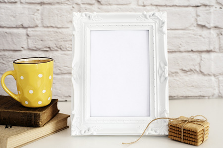 stock photography: Frame Mockup. White Frame Mock Up. Yellow Cup Of Coffee With White Dots, Cappuccino, Latte, Old Books, Cookies. Display Mock-Up, Styled Stock Photography. Empty Rustic Frame. Gray Brick Wall. Leisure Lifestyle Concept. Light Rustic Background