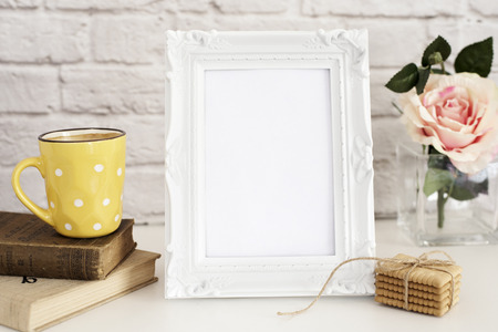 stock photography: Frame Mockup. White Frame Mock Up. Yellow Cup Of Coffee With White Dots, Cappuccino, Latte, Old Books, Cookies. Vase with Flower Rose, Styled Stock Photography. Empty Rustic Frame. Gray Brick Wall. Leisure Lifestyle Concept. Light Rustic Background Stock Photo