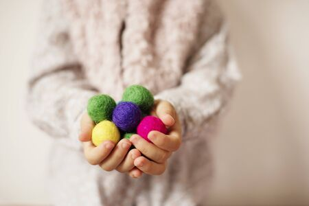 Close up of children hands holding colorful felt balls. Child, kid palms. A little girl keep in handfuls of colored wool balls. Lifestyle concept. Selective focus Stock Photo