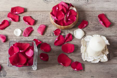 sweetest: Glass vase and wood bow filled with red rose petals, white aromatic vanilla candle. Wooden background. Aromatherapy concept. Romantic background