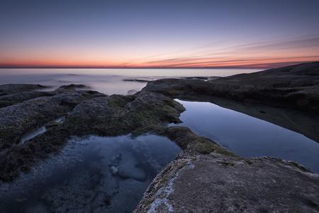 Zeegezicht tijdens zonsopgang. Mooi natuurlijk zeegezicht, blauw uur. Rotsachtige zonsopgang. Overzeese zonsopgang bij de kust van de Zwarte Zee dichtbij Ravda. Stockfoto