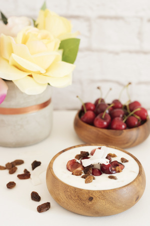 Oat Flakes With Yogurt And Fruits. Cherries, Raisins And Coconut Chips. Overnight Breakfast. Healthy Food Concept. Fitness Mood Diet. Summer Light Snack. Bright Brick Wall Background.