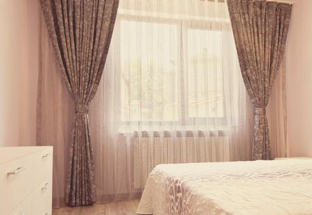 De longs rideaux de luxe et des rideaux de tulle sombres sur une fenêtre de la chambre. Concept de design d'intérieur. Teinture vintage, filtre photo