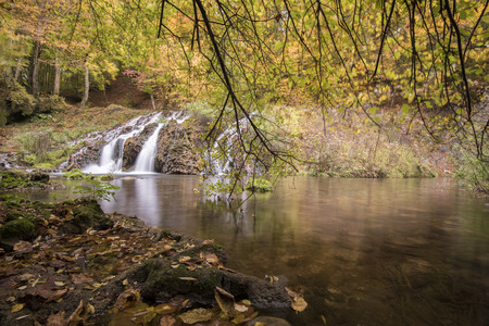 flowing water: Waterfall in the forest during autumn. Beautiful view of a river with an waterfall in the forest Stock Photo