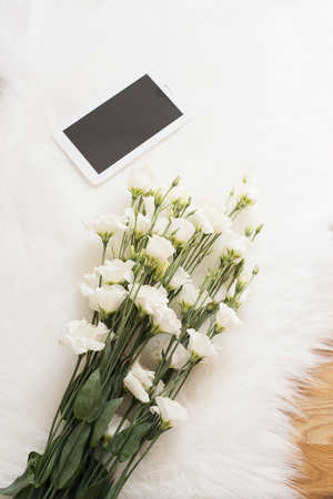 luxury room: A large bouquet white flowers and tablet on the floor on a white fur carpet. Cozy, fashion comfortable femininity home workplace. Flat lay style. Top view, vertical image Stock Photo