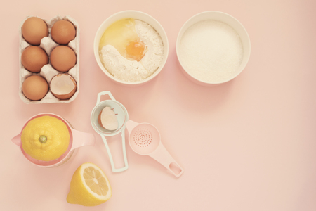 Ingredients and kitchen bake tools for cooking lemon cake or sweets - eggs, flour, sugar, hand juicer on a pastel punchy pink background. Top view of a holiday baking still life Stock Photo