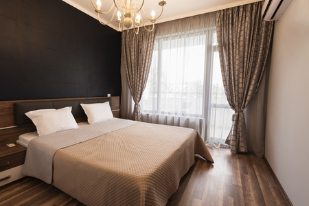 Modern bedroom interior design. Luxury bed room with brown color tone. Windows with long curtains and sheers. Banque d'images