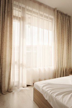 Hotel interior. Long beige curtains and tulle curtains, sheers on a window in the bedroom. Interior design concept.