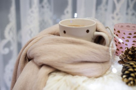 Hot chocolate, a cup of cappuccino on a fur chair in front of a large window with a white sheers curtain. Warm scarf, cones and lights around. Cozy winter evenings
