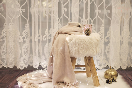 Hot chocolate, a cup of cappuccino on a fur chair. Warm scarf, cones and lights around. Cozy winter evenings