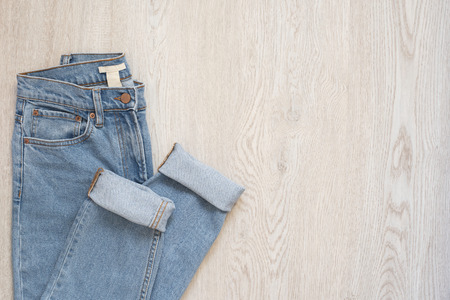 Blue jeans on a wooden background. Flat lay of female styled look. Top view. Shopping Concept. Fashion Outfits 免版税图像