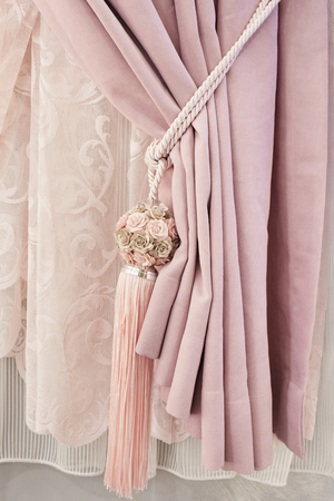 Part of beautifully draped curtain on the window in the room. Floral tassel tieback. Close up of piled curtain. Pink luxury curtain, home interior decor Standard-Bild - 116503285