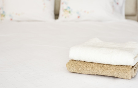 Clean bath towels on bed in hotel suite