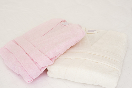 Folded bathrobe on bed in room. White and pink, two robes