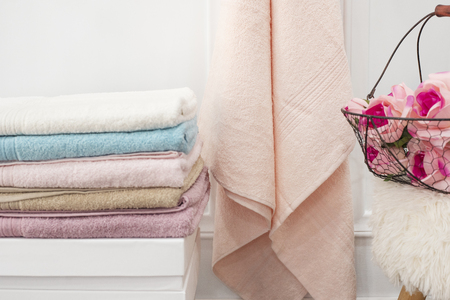 Clean soft colorful towels. Flowers on background Imagens
