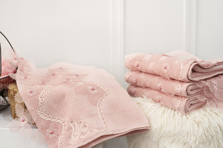 Stack of clean soft pink towels with lace and pearls Imagens
