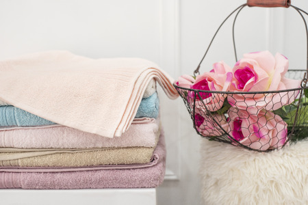 Stack of clean soft colorful towels. Flowers on background Imagens