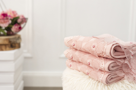 Stack of clean soft pink towels with lace and pearls. Flowers on background