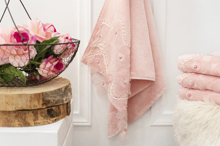 Clean soft pink towels with lace and pearls. Flowers on background