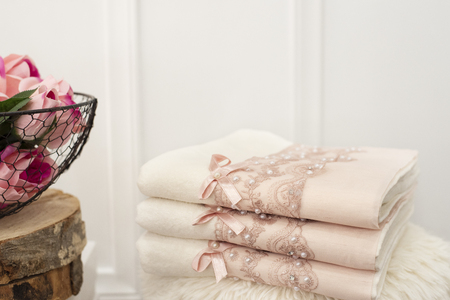 Stack of clean soft white and pink towels with lace and pearls. Flowers on background