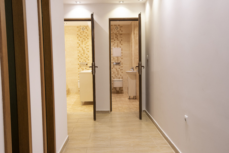 Two open doors to big modern bathroom and toilet. Home interior