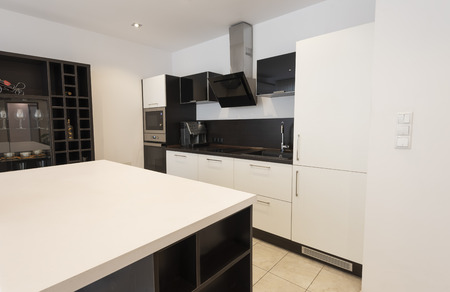 Modern new light interior of kitchen with white and black furniture Imagens