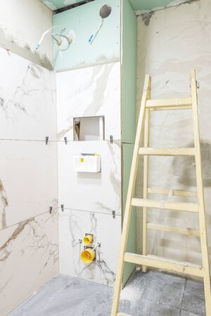 Bathroom renovation concept. Marble ceramic tiles with spacers and grey cement walls in bathroom, renovating and working in toilet, space for text. Repairing