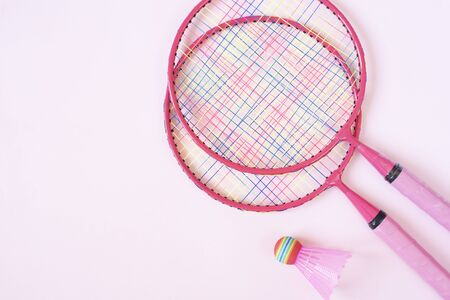 Badminton equipment. Badminton rackets and shuttlecock on pink background. Top view, copy space