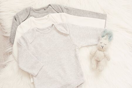Baby Bodysuit Mockup. Styled Stock Photography. Clothes and Bunny Toy For A Boy. Jumpsuits, Rompers On A White Fur Carpet. Newborn Baby Concept. Baby Boy Clothes Set