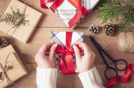 Sfondo Di Natale. Mani Femminili Che Legano Un Fiocco Rosso. Donna che imballa i regali di Natale. Concetto di vacanza. Vista dall'alto, piatto, regalo dell'Avvento Archivio Fotografico